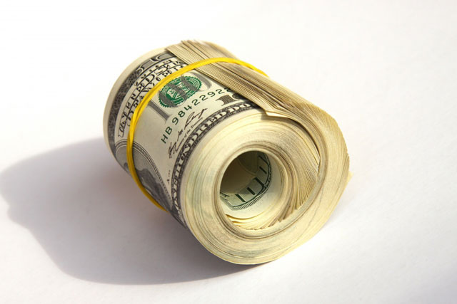 Банкноты долларов, скрученные резинкой